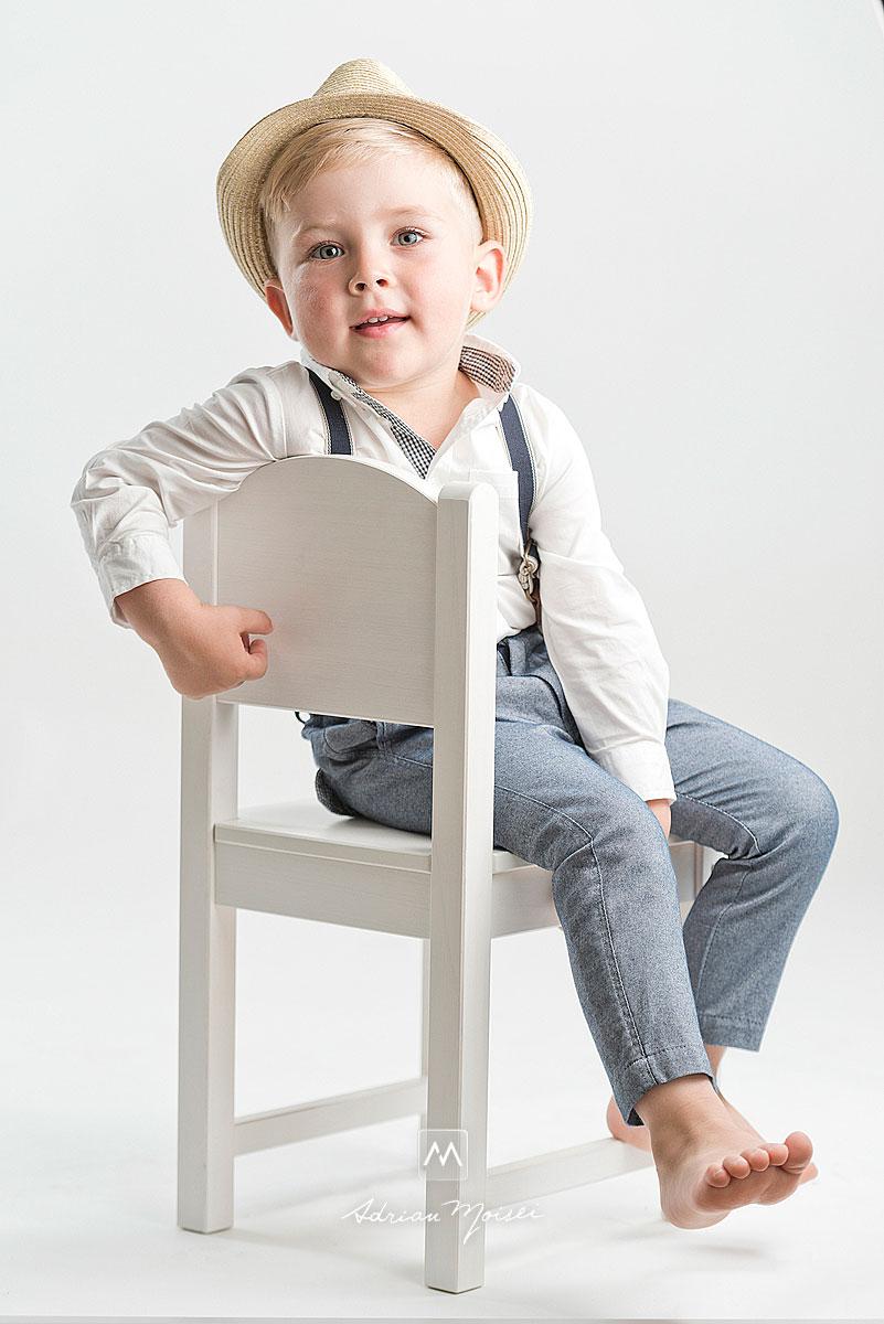 Baietel blond de 4 ani, cu palarie, desculti. Sta pe un scaun alb si se simte confortabil la sedinta foto de copii