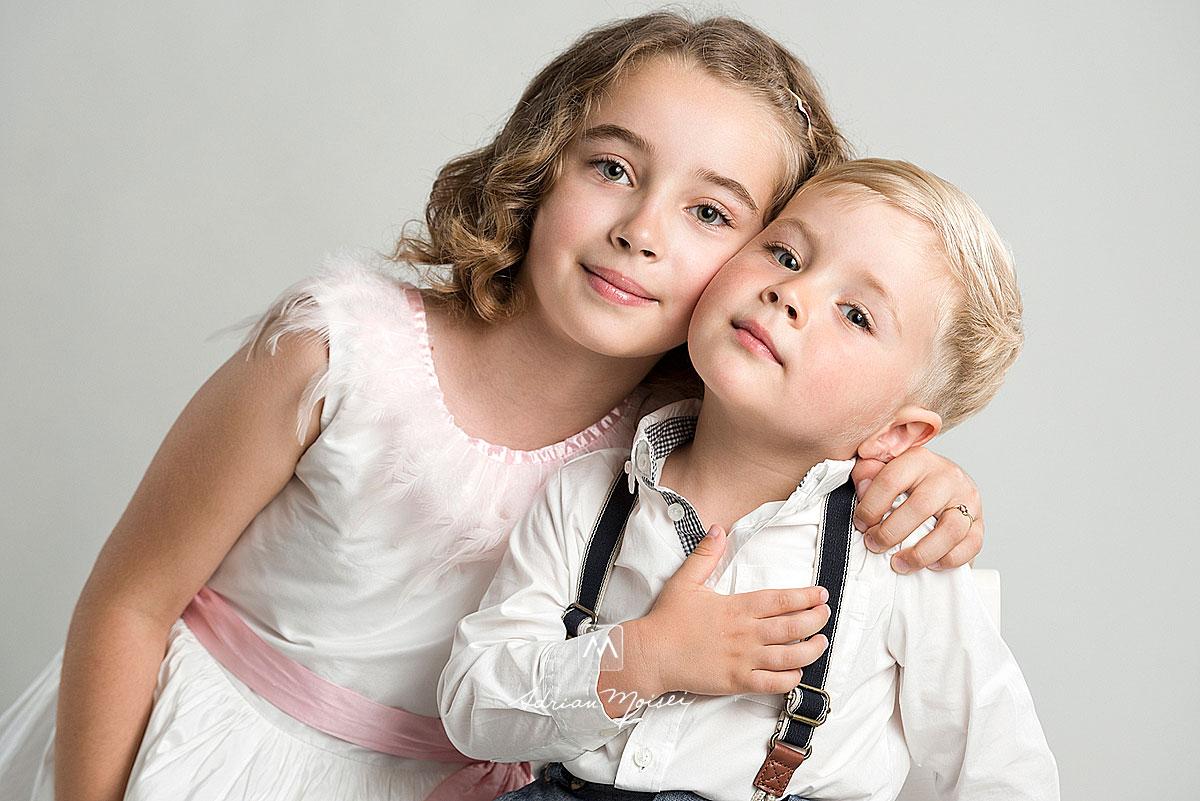 Copilas blond, in camasa alba cu bretele la sedinta foto de copii