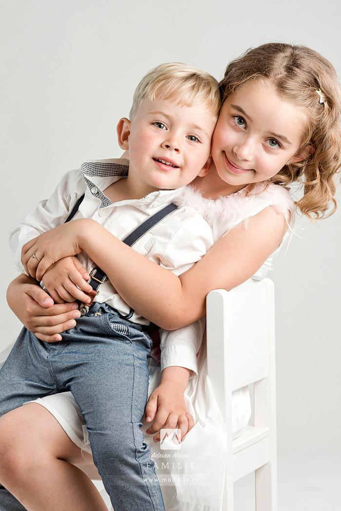 Frati imbratisandu-se, stau pe scaun la o sedinta foto de portret copii