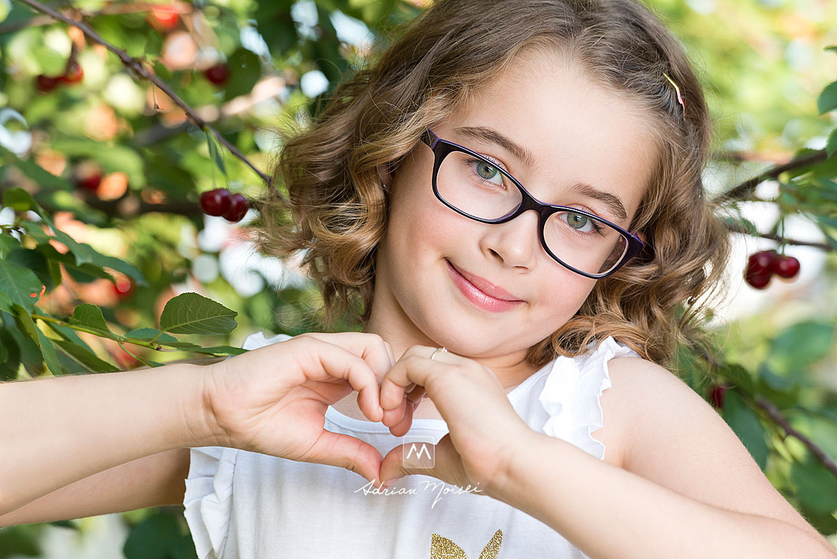 Fetita de 8 ani, facand cu mainile o inima, zambind, fotograf Iasi, Adrian Moisei
