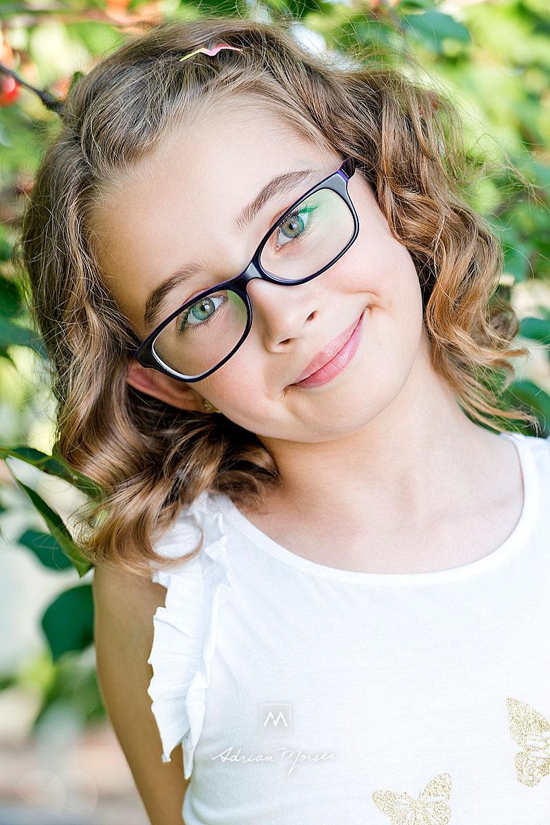 Fetita cu ochelari, portret in livada cu visine