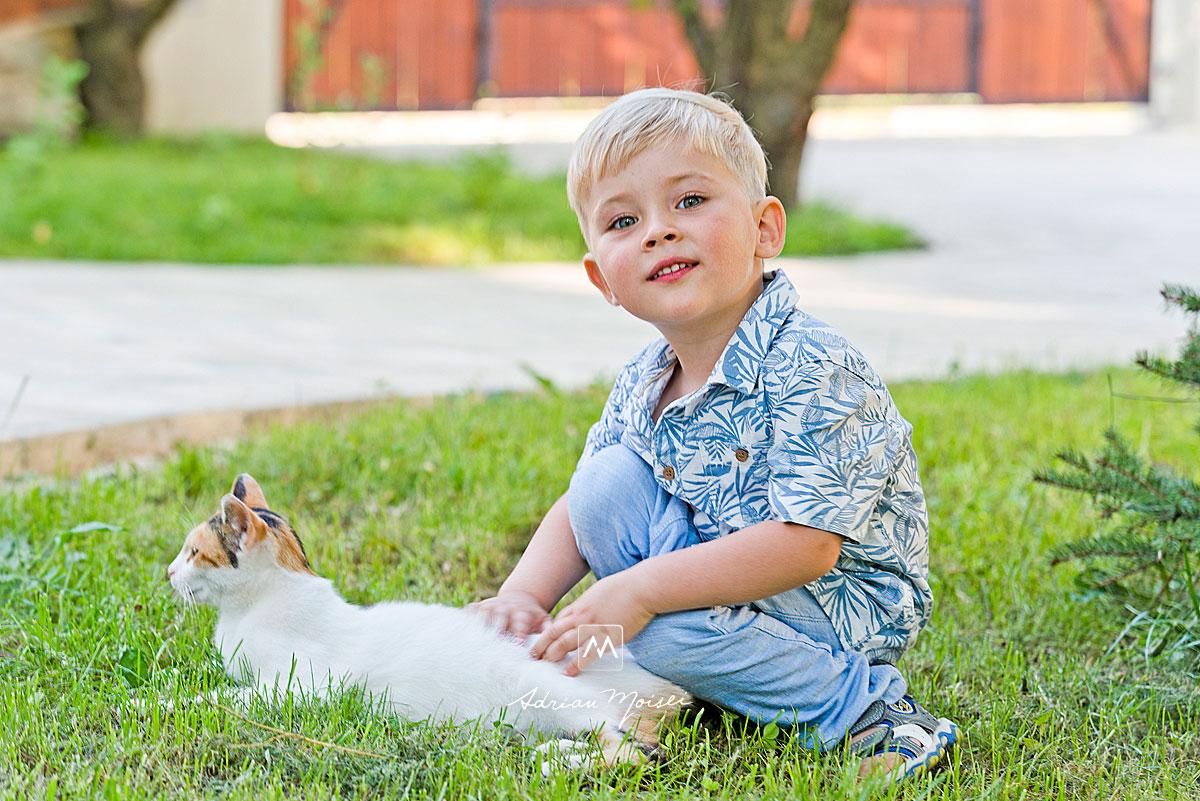 Baietel de 4 ani, jucandu-se cu pisica in iarba