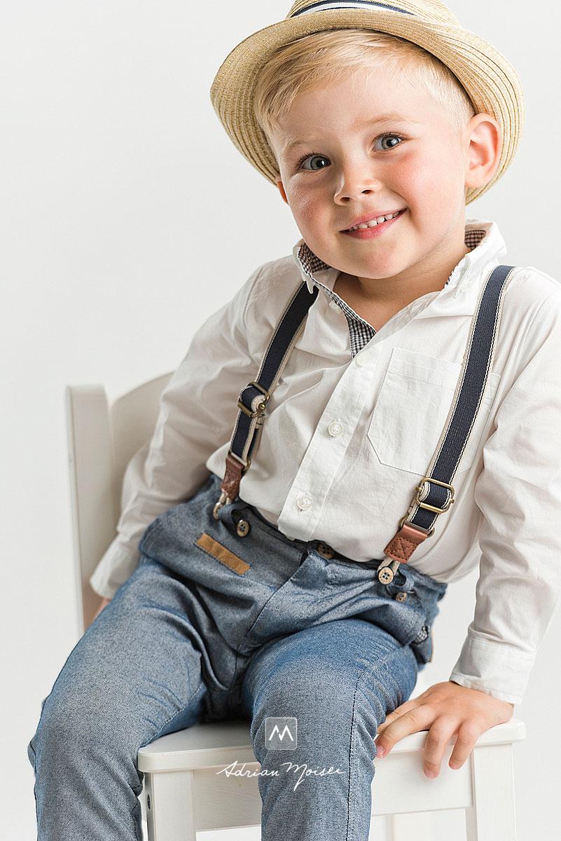 Copilas de 4 ani, blond, cu palarie, aratand cu degetul spre camera fotografului Adrian Moisei