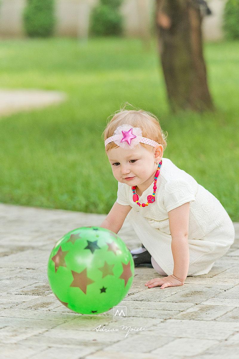 Fetita jucandu-se cu o minge verde, plina de stele