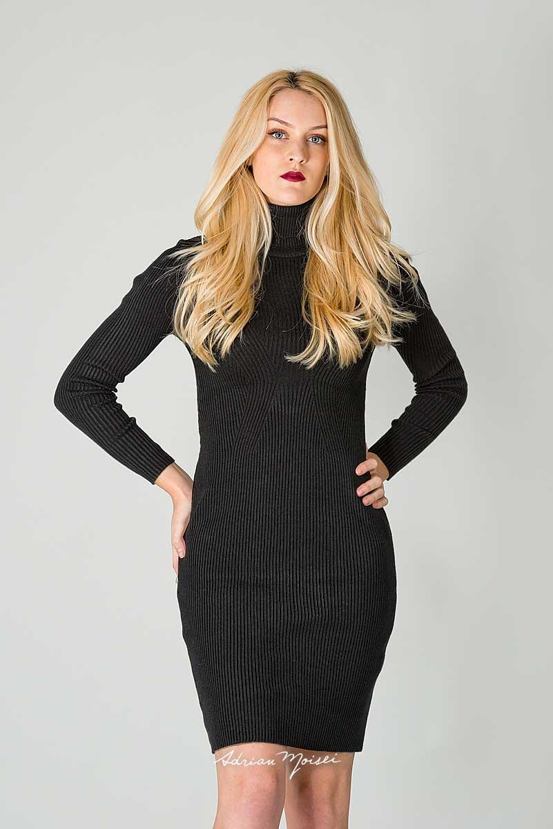 Fotografie de studio cu un model de fashion zambind, cu bluza neagra
