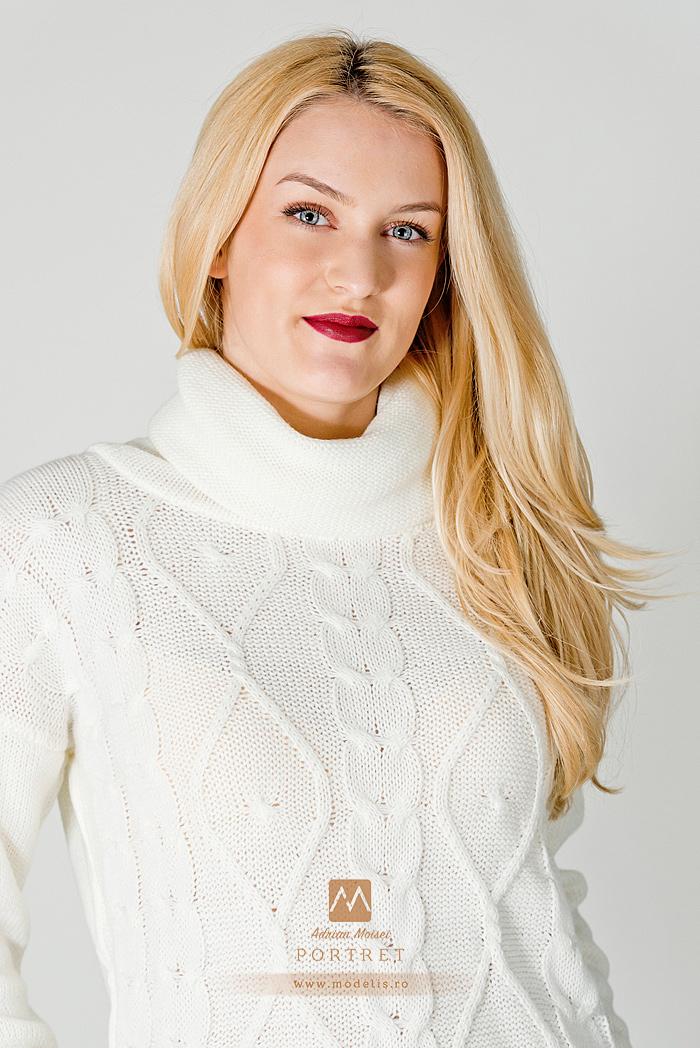 Fotografie de studio cu un model de fashion zambind, cu un pulover alb