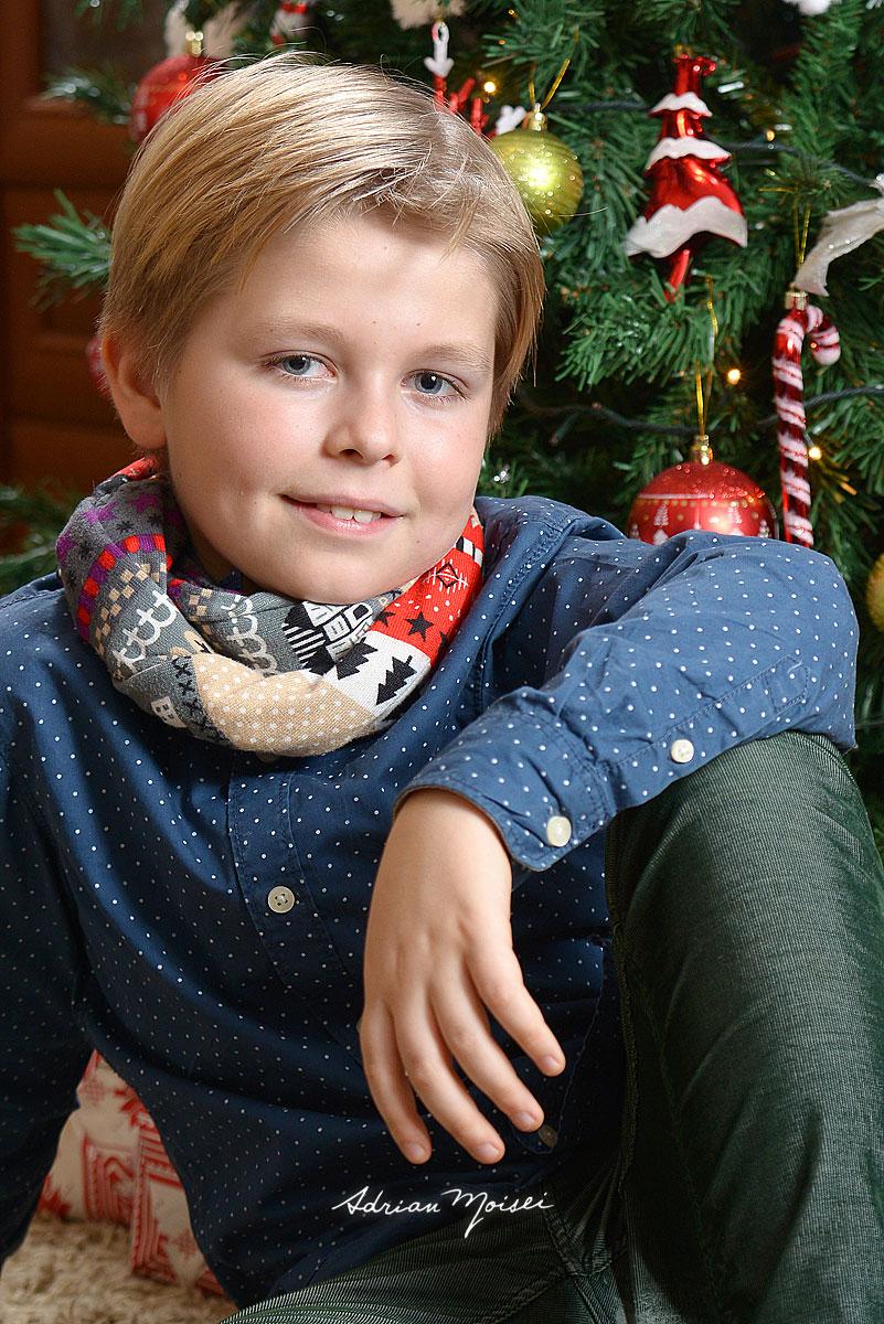 Copil blond langa bradul de Craciun, zambind pentru camera foto