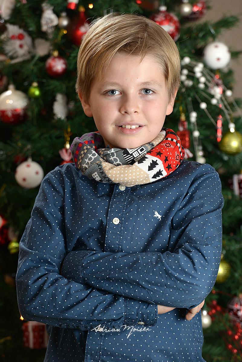 Copil de 10 ani, blond, fotografie de Craciun, cu bradul plin de globuri in fundal. Fotograf Iasi