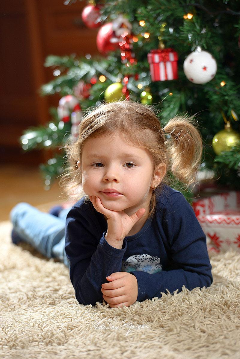 Fetita somnoroasa langa bradul de Craciun intr-o fotografie de familie, asteptandu-l pe Mos Craciun