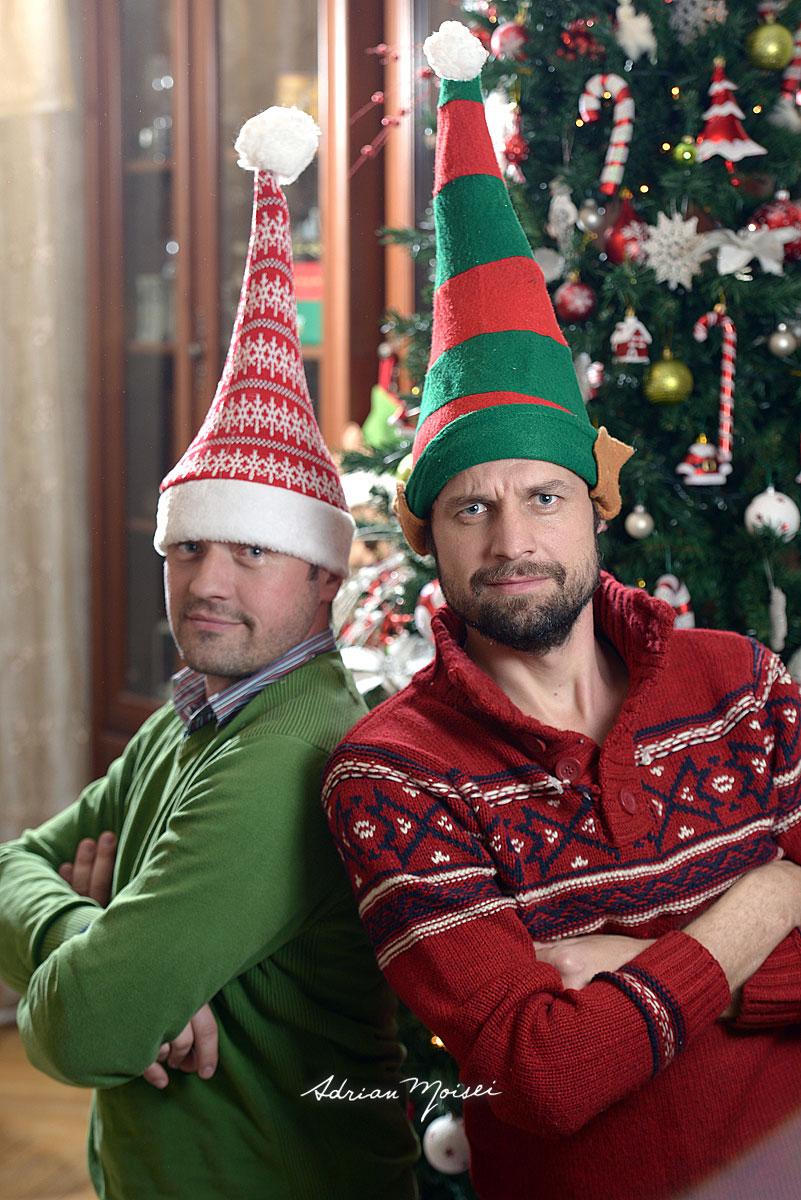 Doi barbati barbosi cu caciulite de elf pe cap, manile in san, intr-o fotografie ce sarbatoreste prietenia de Craciun.
