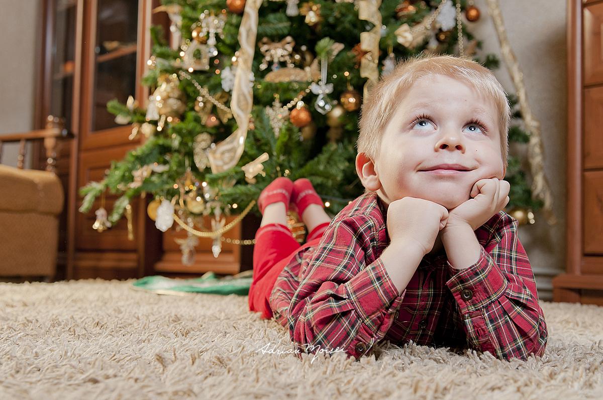 Copilas asteptandu-l pe Mos Craciun, langa pom, fotograf copii