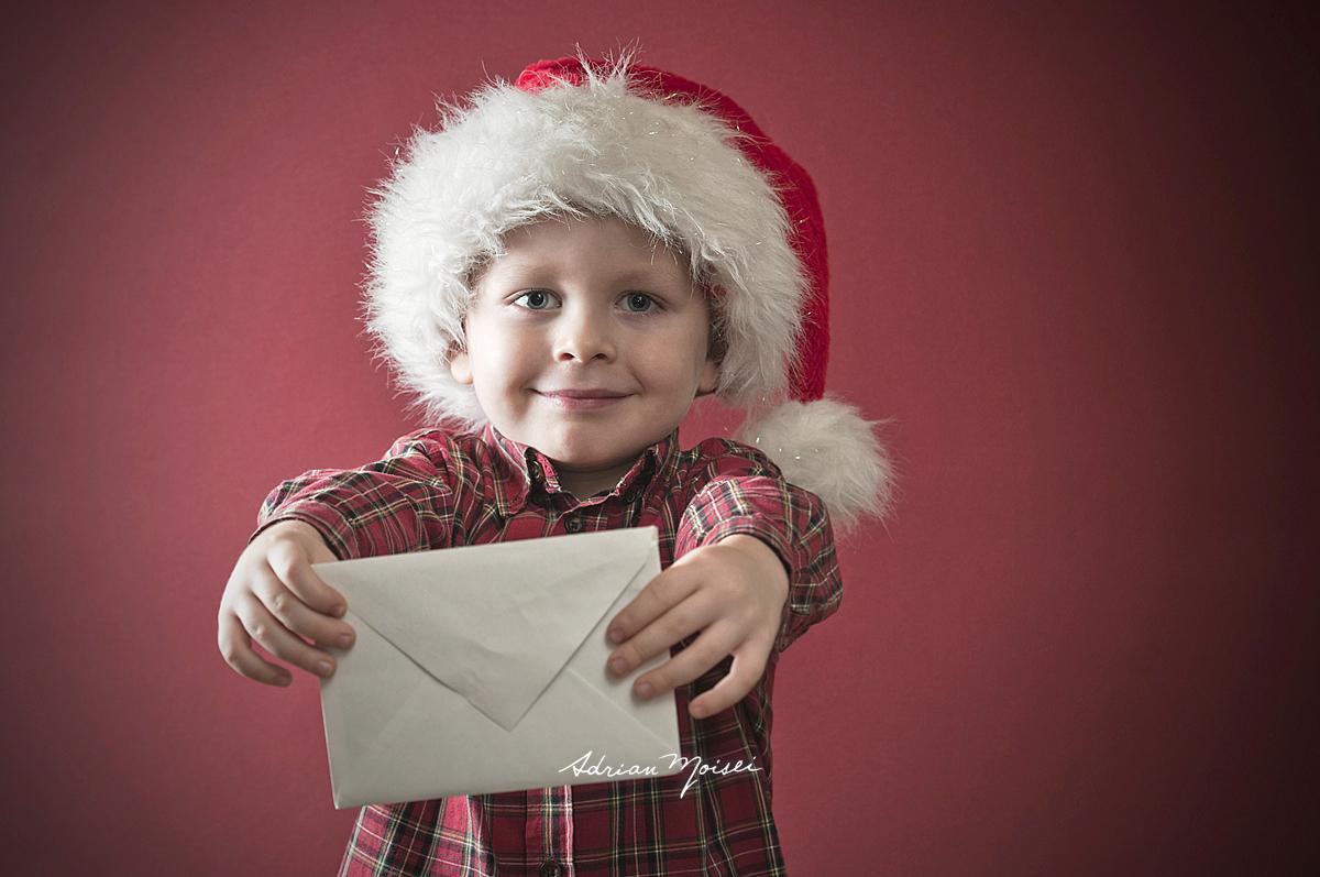 Portret de copil cu scrisoare pentru Mos Craciun in mana