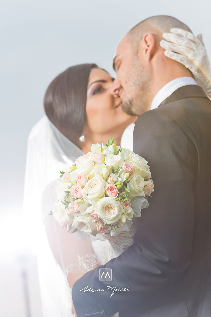 Buchetul miresei cu trandafiri albi, mirele și mireasa în fundal, fotograf nuntă Iași Adrian Moisei, fotograf nuntă Iași