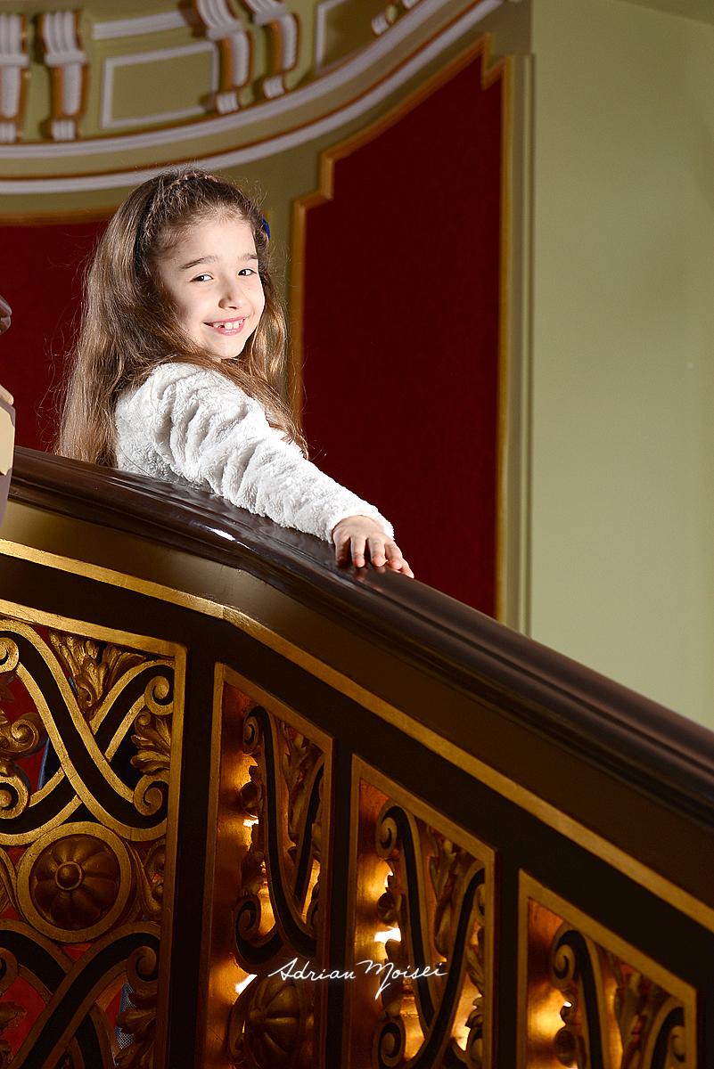 Fotografie copil cu mana pe balustrada