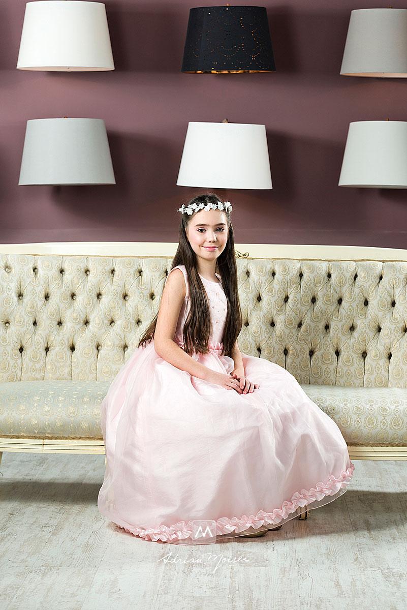 Copila pe canapea, cu coronita si un zambet magic
