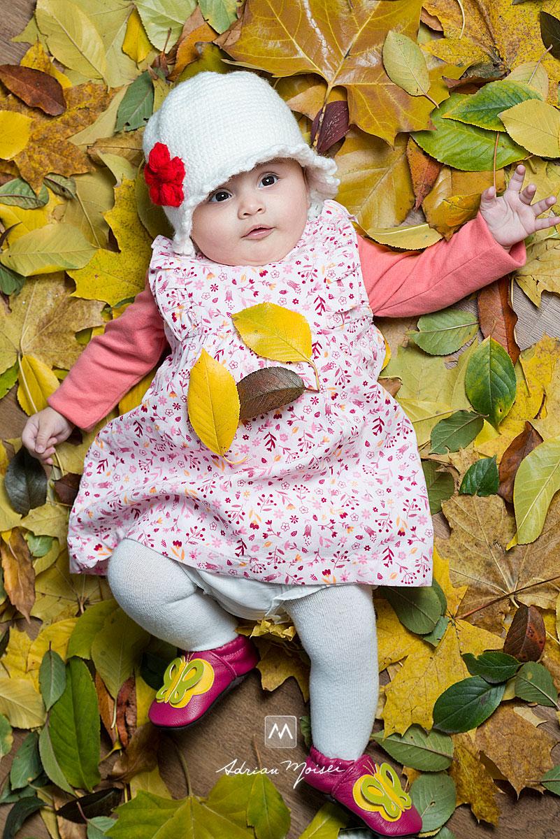 Fotografie bebelus pe un pat de frunze de toamna