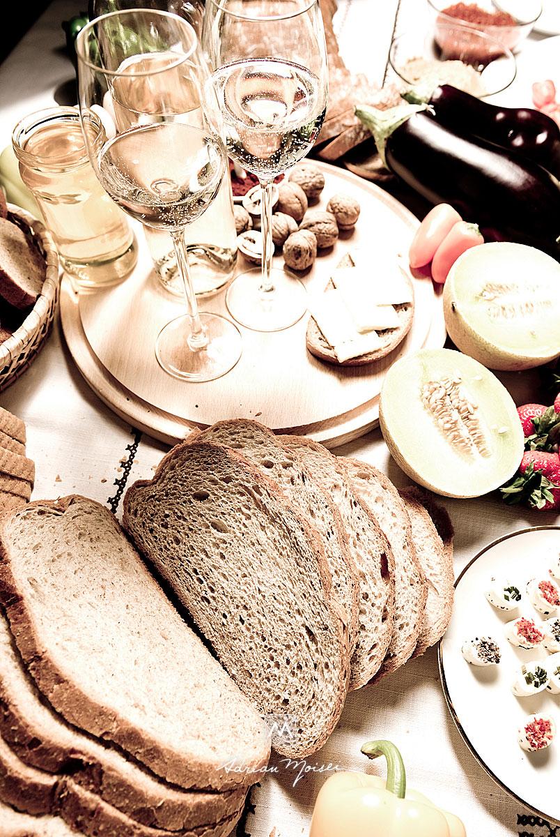 Painea Panifcom pe o masa plina de: legume, vin, branza, fructe, capsuni, ardei iute