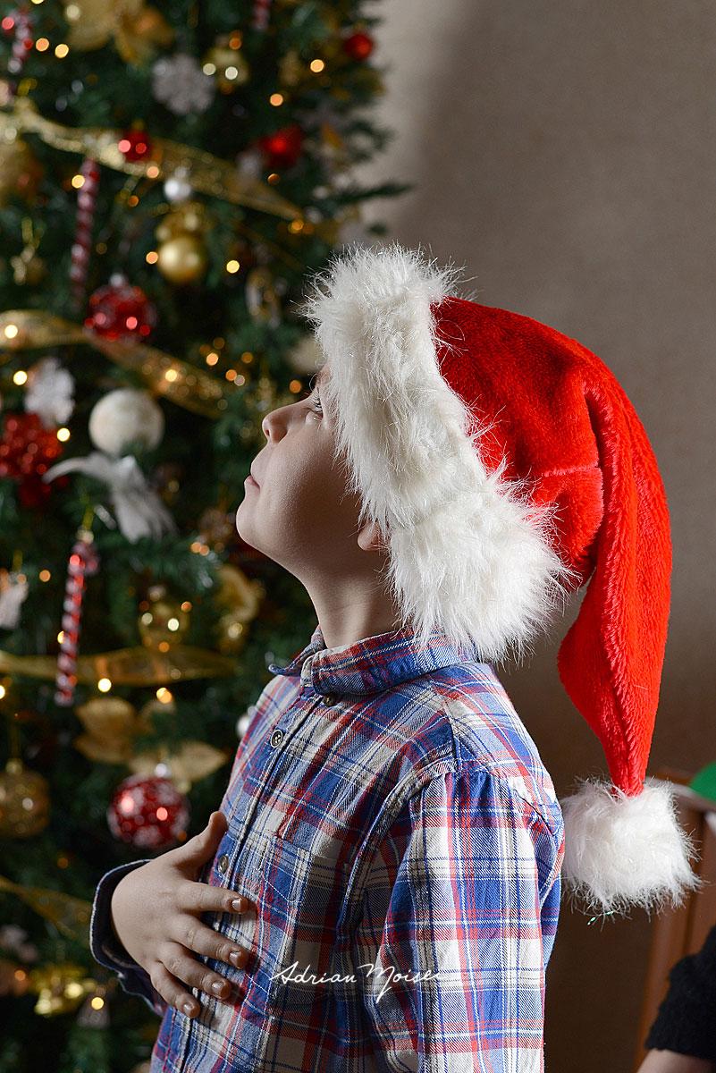 Copilas langa bradul de Craciun gandindu-se la ce cadou ar prefera de la Mos Craciun, fotografie in locatie