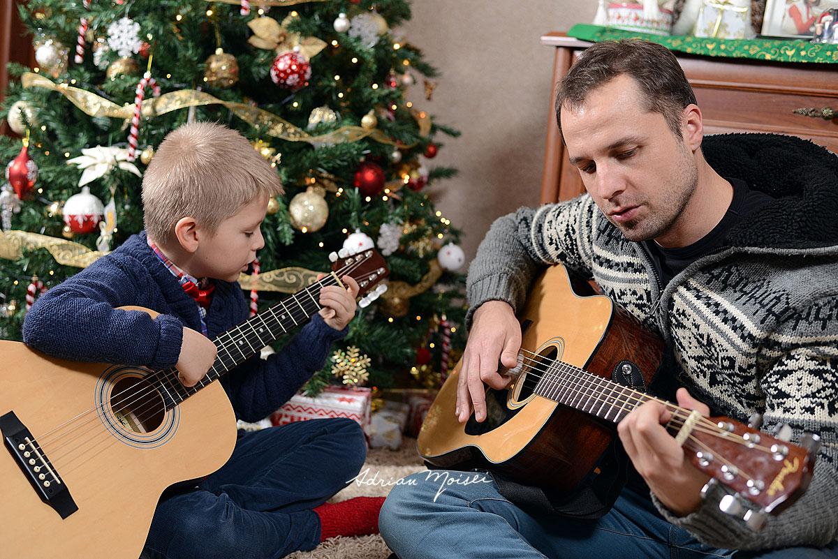 Tata si fiu, langa bradul de Craciun, cantand la chitara. Fotografie de familie realizata de Adrian Moisei fotograf Iasi
