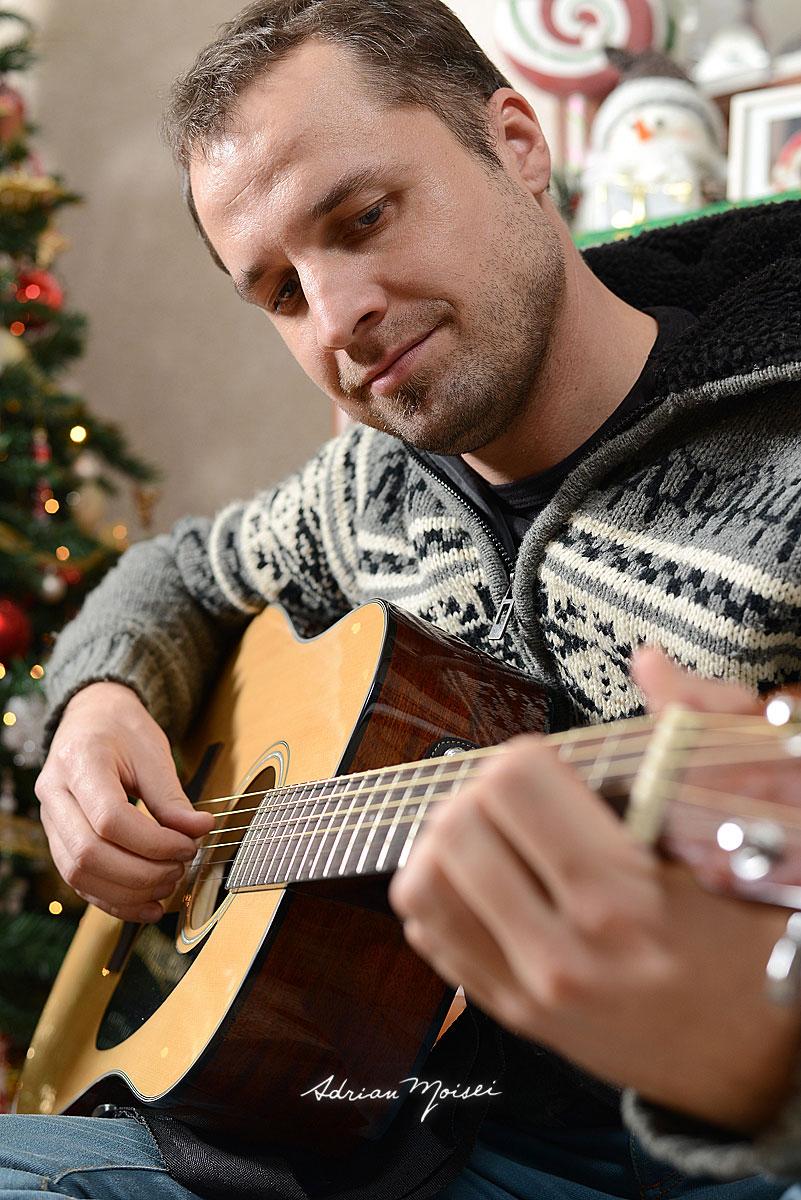 Portret de barbat cantand la chitara, de Craciun. Fotografie de portret