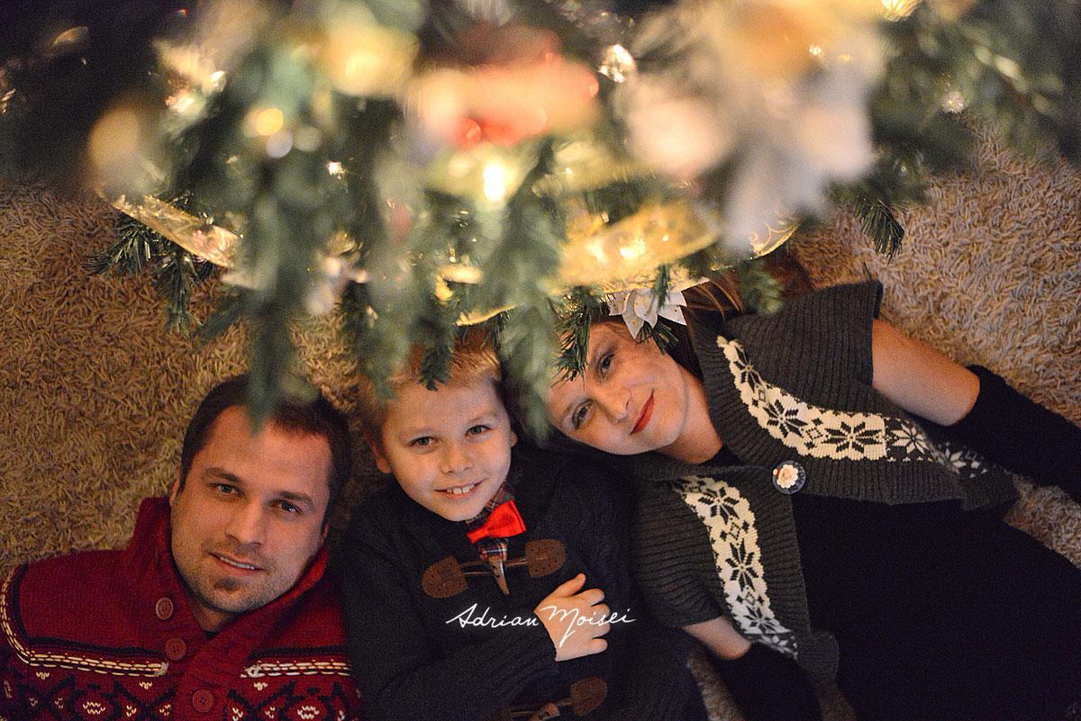 Familie formata din mama tata si fiu, sub bradul de Craciun, pe spate. Fotograf familie Iasi, Adrian Moisei