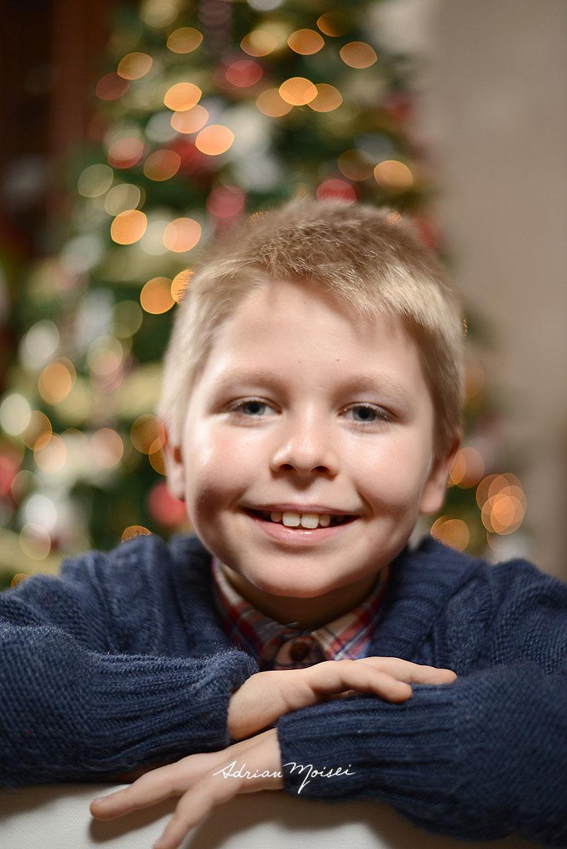 Portret copilas de 10 ani cu adancime de camp mica si bradul de Craciun in fundal