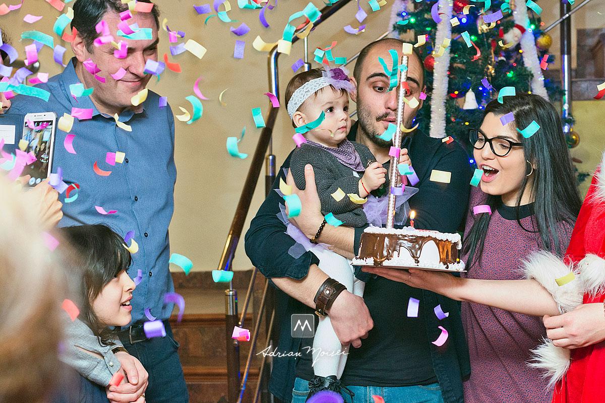 Familie sarbatorind cu un tort in fata