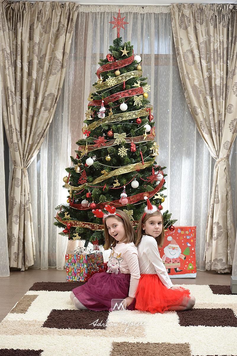 Doua fetite, surori, langa pomul de Craciun