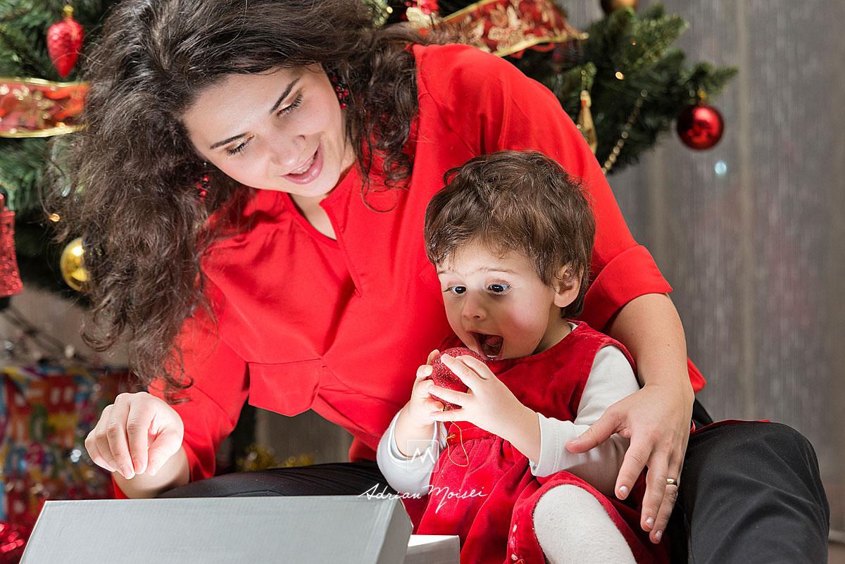 Fetita uimita de un glob, langa mama ei, fotografii de Crăciun în Iași