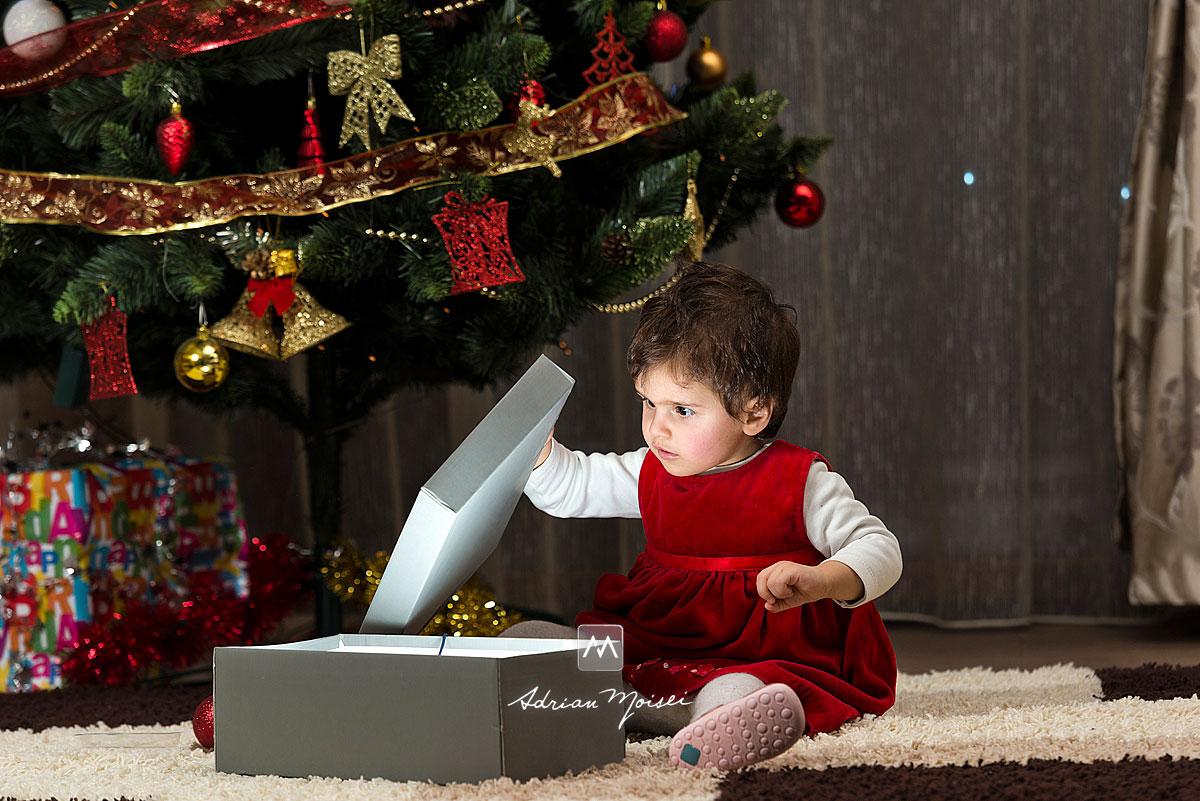 Fetita deschizand o cutie magica de Craciun, langa brad, fotografii de Crăciun în Iași