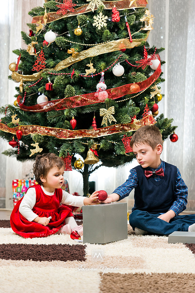 O fata si un baiat, frati, jucandu-se langa bradul de Craciun, fotografie de familie de Adrian Moisei, fotografii de Crăciun în Iași