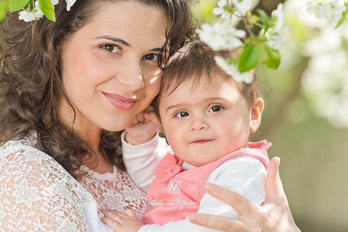 Bebelus in bratele mamei sale, intr-o livada inflorita