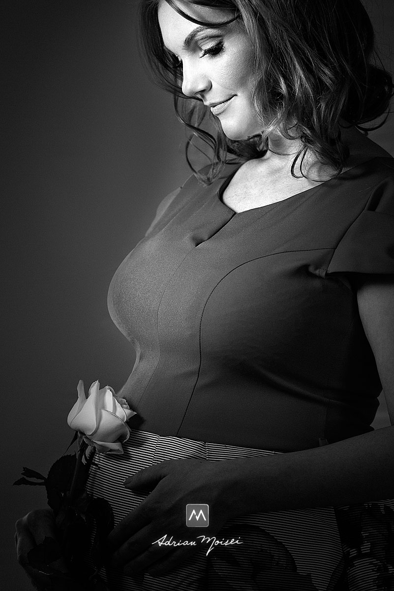 Portret alb negru de femeie insarcinata cu un trandafir alb