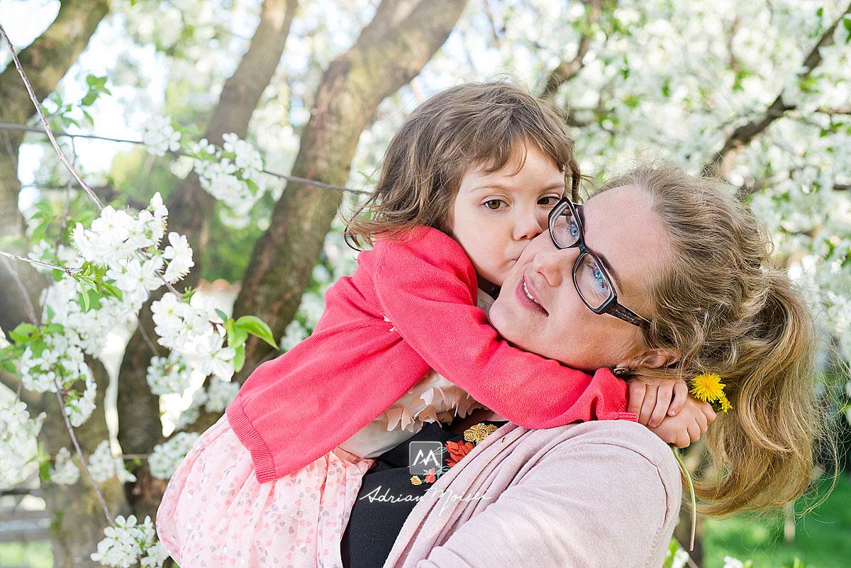 Fotografie de familie în livada înflorită de vișini, alături de un copilaș adorabil, fotografie în natură, fotograf de familie Iași