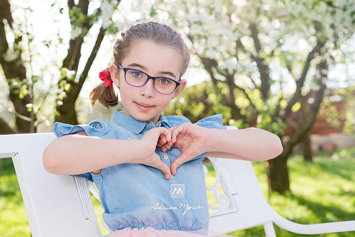 Fetita relaxata pe o banca alba, in gradina de la studioul fotografului iesean Adrian Moisei, fotograf de familie Iași