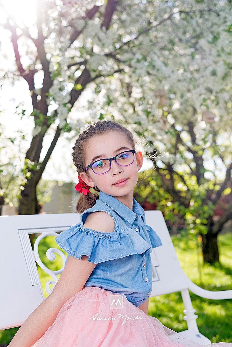 Fetita cu ochelari, pozand in timp ce sta pe o banca, fotograf de familie Iași