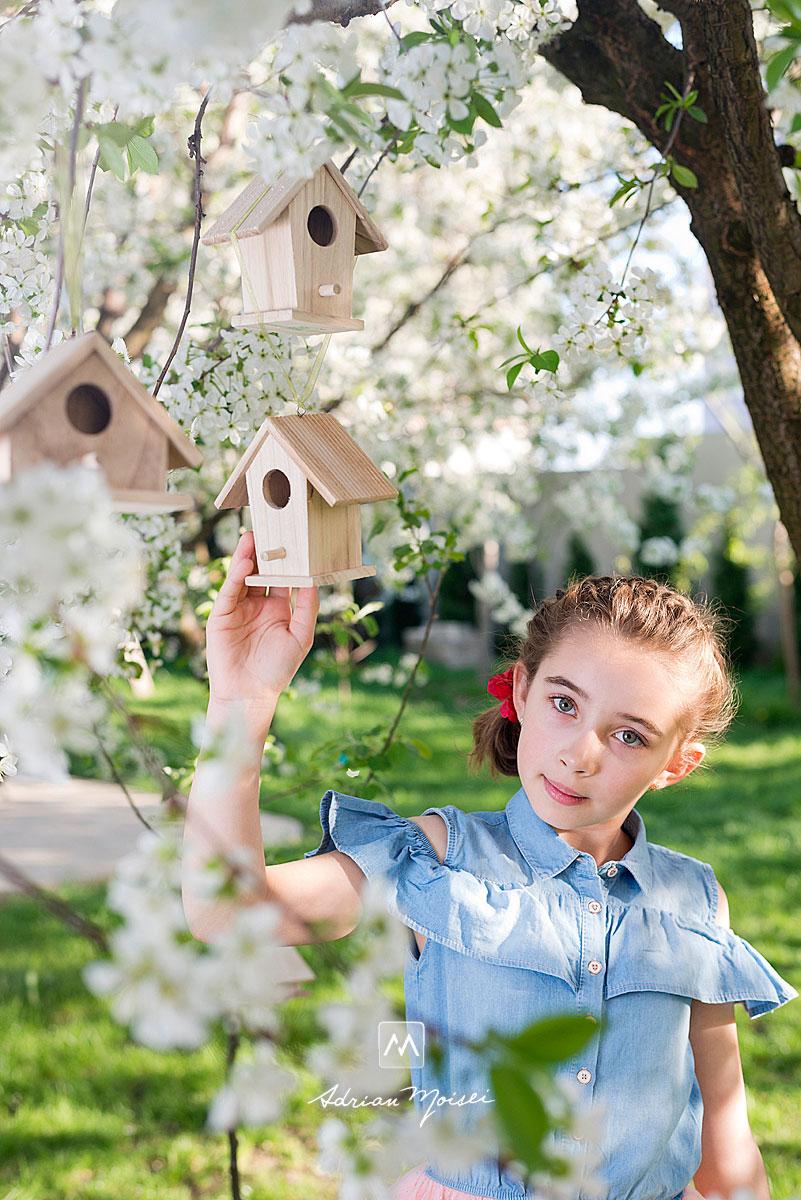 Fetita in livada inflorita a studioului lui Adrian Moisei, fotograf Iasi, si custile de vrabiute, fotograf de familie Iași