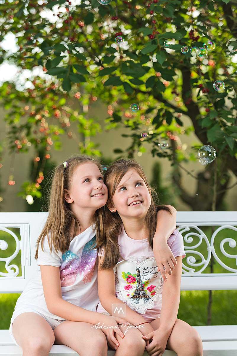 Două surori în livada de vișini, distrându-se, jucându-se cu baloane de săpun, în livada sa de la studio, fotograf de familie Iași