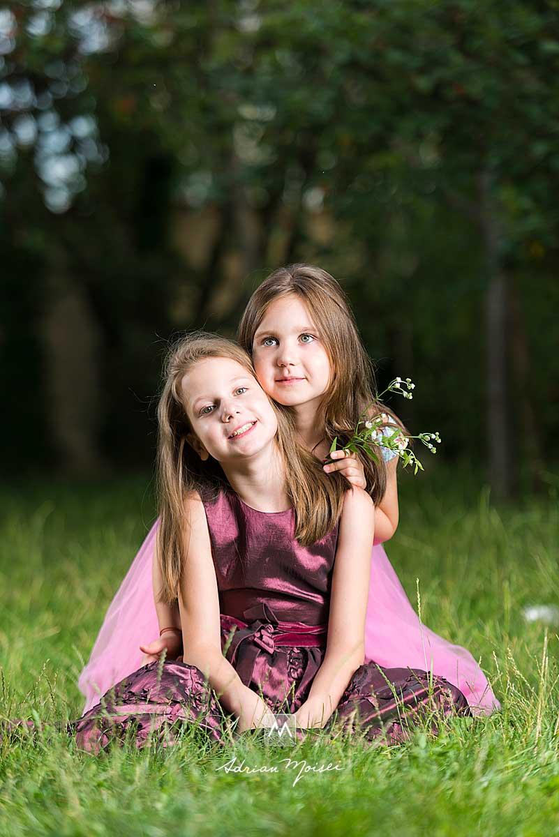 Fotografie cu două surori în livada de vișini, distrându-se, jucându-se cu baloane de săpun, în livada sa de la studio, fotograf de familie Iași