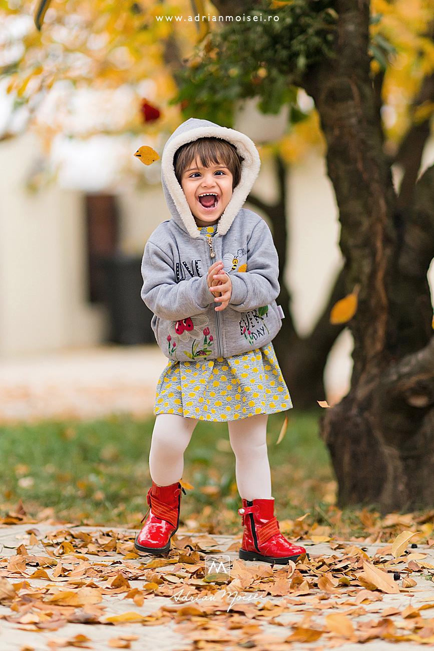 Fetita de 2 ani cu cizmulite rosii, razand fericita, fotografie de familie, intr-o livada minunata, realizata de Adrian Moisei, fotograf de familie Iași