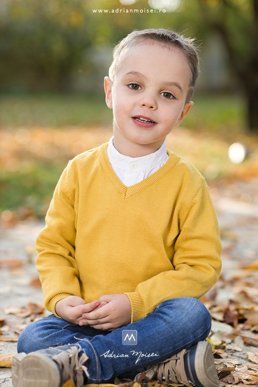 Copilaș de 3 ani în parc, stand printre frunze de toamna, fotograf de familie Iași