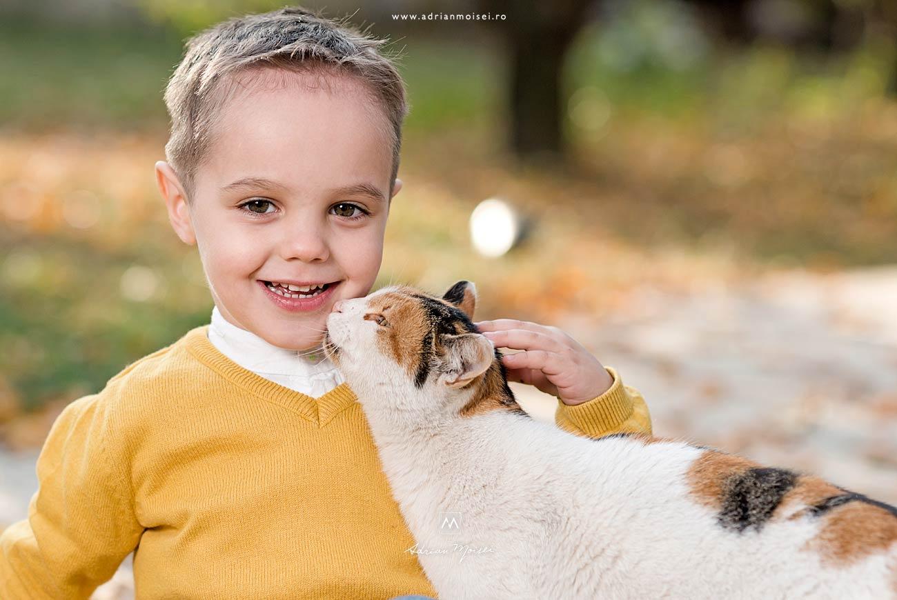 Copilaș de 3 ani și o pisica curioasă care-l miroase la gurita. Fotograf de familie în Iași, Adrian Moisei, fotograf de familie Iași