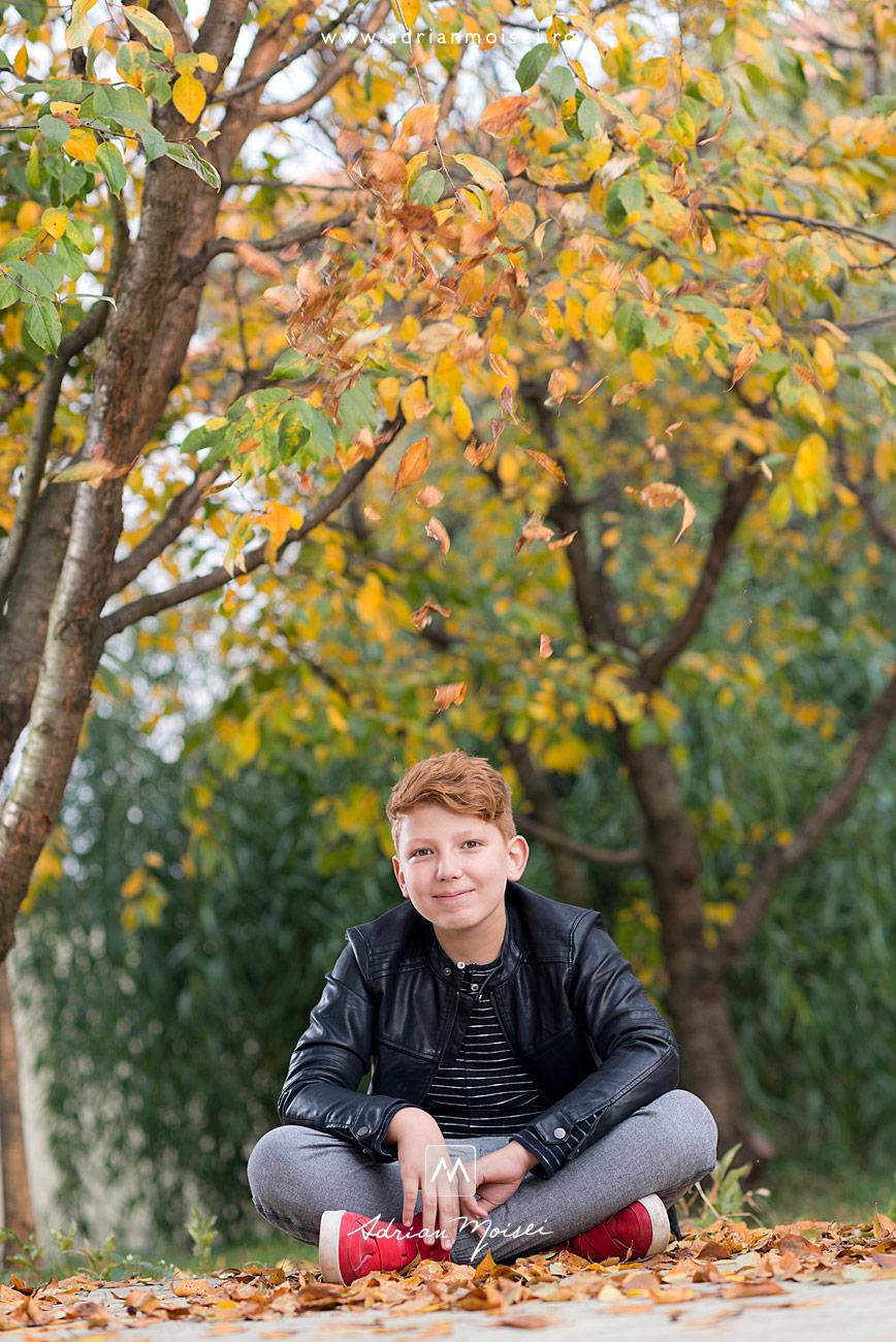 Adolescent stand turceste intre frunze de toamna, fotograf de familie Iași