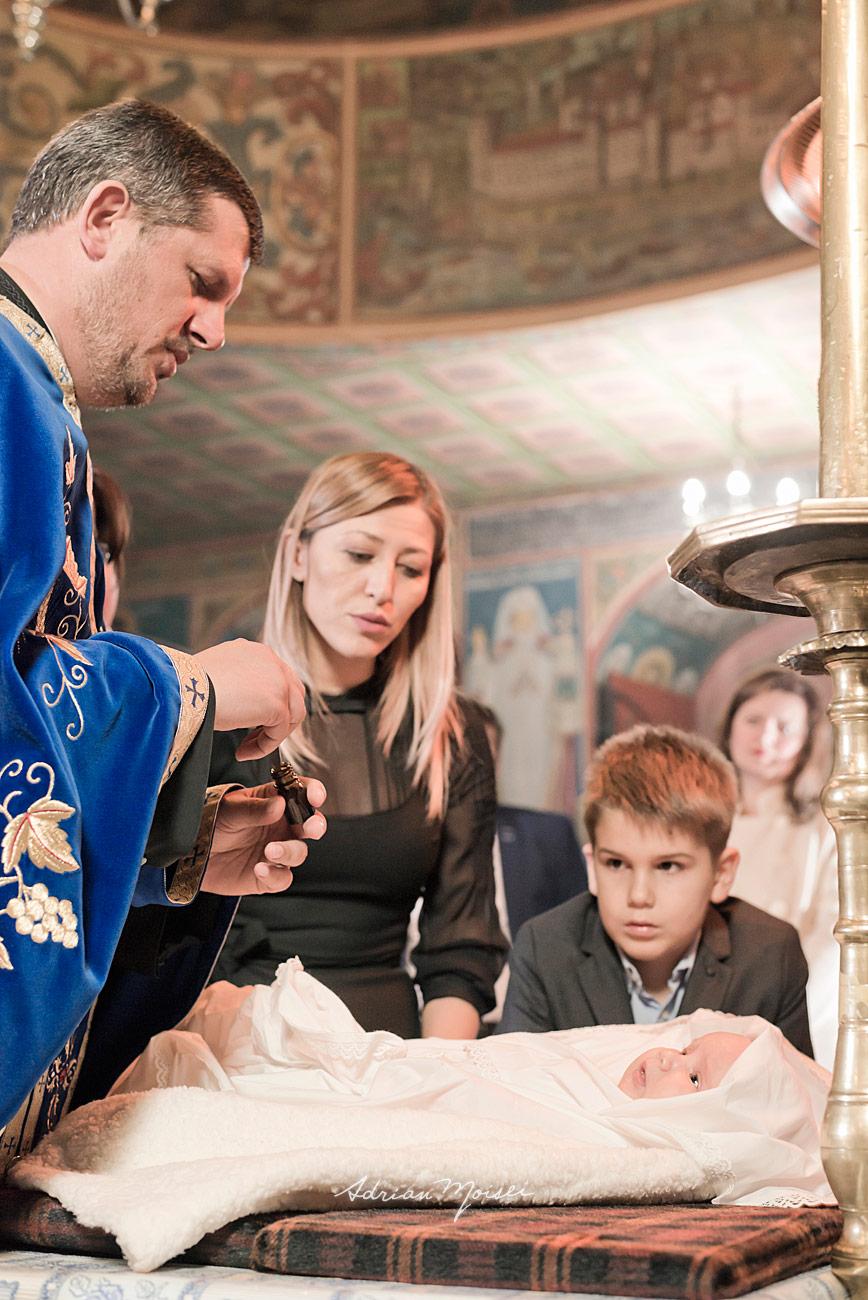 Preot care miruieste nou-nascutul la biserica Bărboi Iasi, fotograf botez Iași