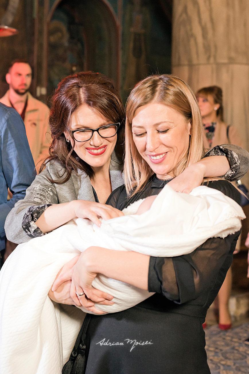Mama si nasa de botez zambind la nou nascut, fotograf botez Iași