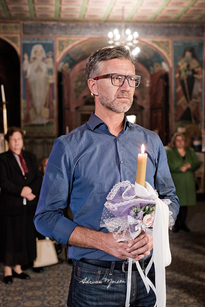 Portret de nas de botez, tinand lumanarea în mână, fotograf botez Iași