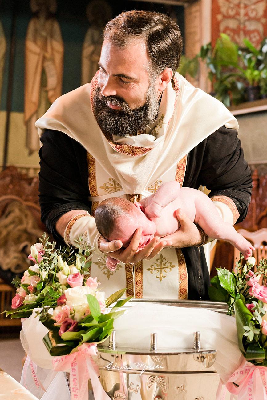 Scoaterea din cristelnita a bebelusului botezat