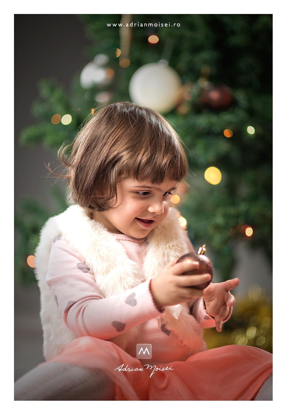 Fetita vesela jucandu-se cu globurile - Minisesiune foto de Crăciun, fotografie de familie, Adrian Moisei fotograf Iași, fotograf de familie Iași