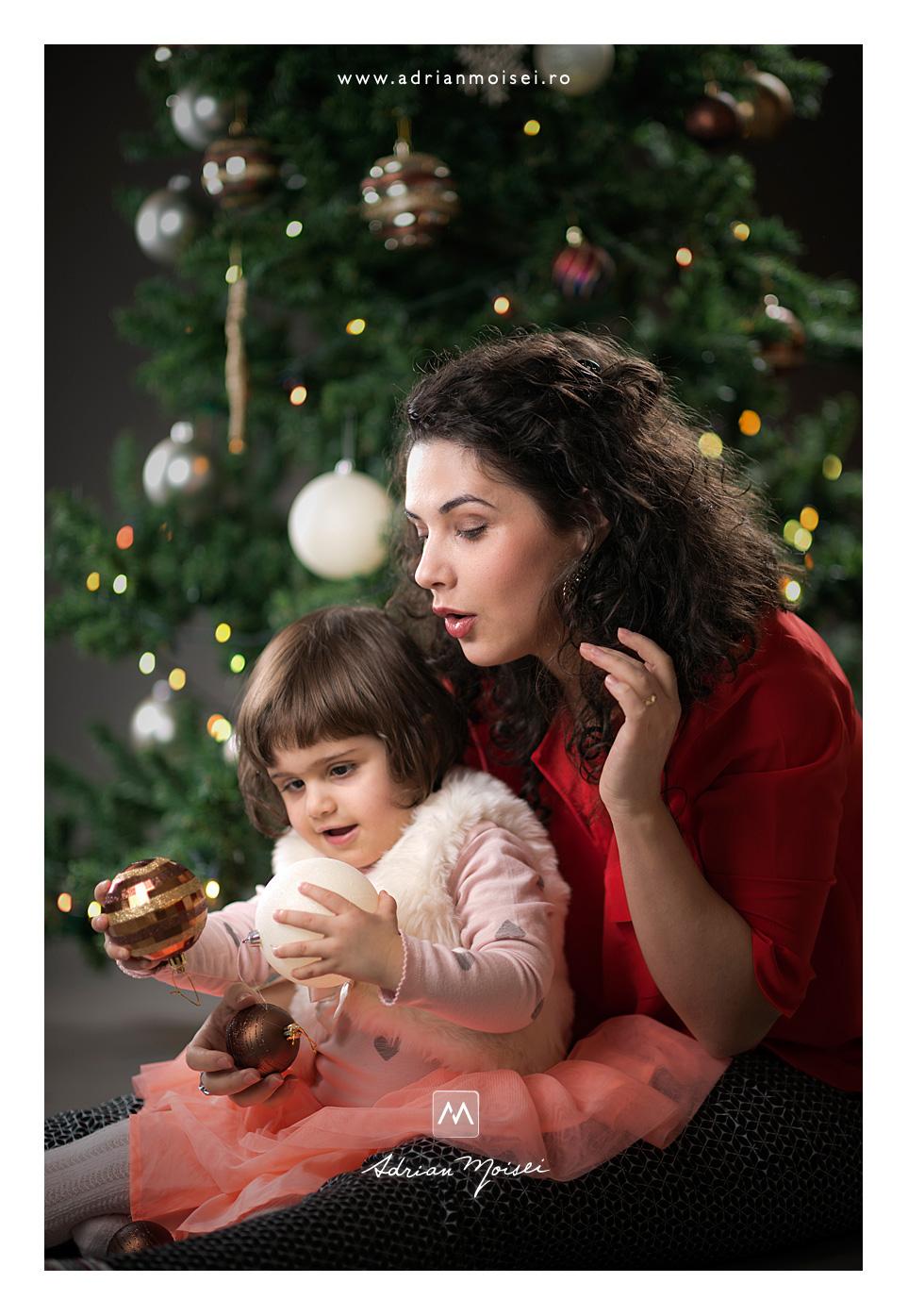 Fetita vesela jucandu-se cu globurile - Sesiune foto de Crăciun, fotografie de familie, Adrian Moisei fotograf Iași, fotograf de familie Iași