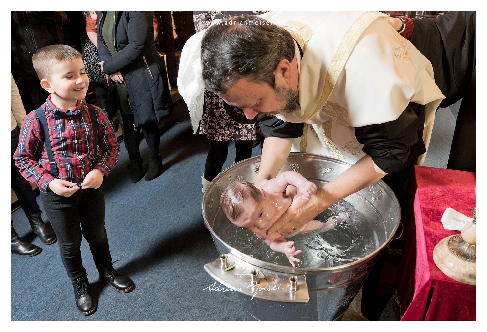 Bebeluș botezat în cristelniță de către un preot cu har, sub privirile curioase ale frățiorului său, la Iași, biserica Sfântul Nicolae Domnesc